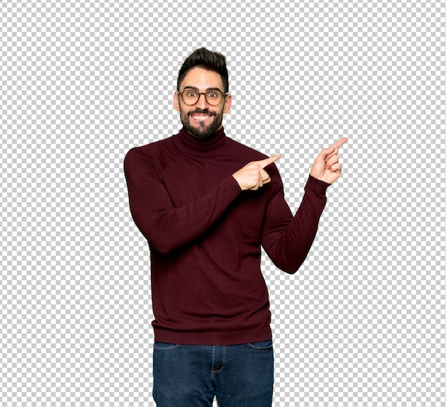 Handsome man with glasses frightened and pointing to the side