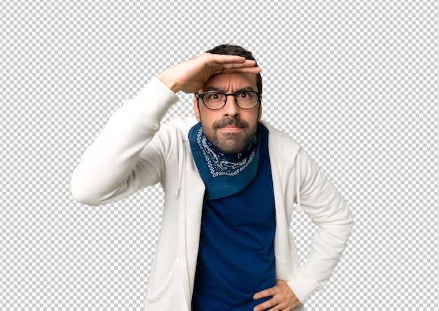 Handsome man with glasses looking far away with hand to look something