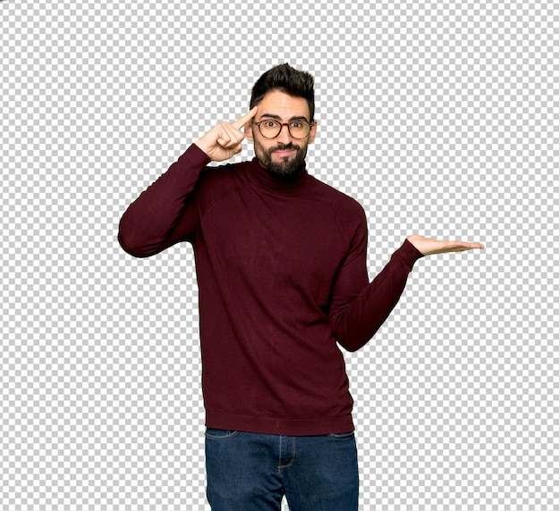 Handsome man with glasses making the gesture of madness putting finger on the head