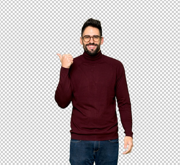 Handsome man with glasses pointing to the side to present a product