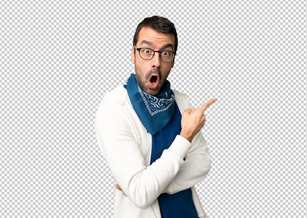 Handsome man with glasses surprised and pointing side