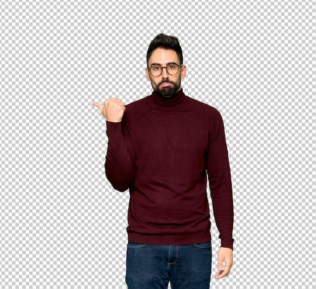 Handsome man with glasses unhappy and pointing to the side
