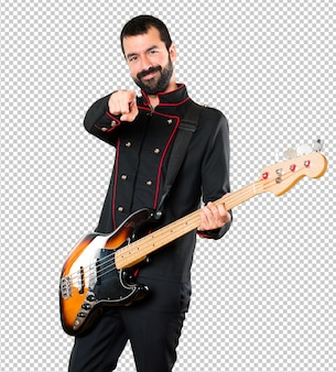 Handsome man with guitar pointing to the front