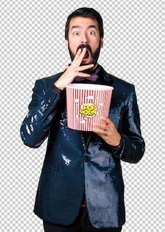 Handsome man with sequin jacket eating popcorns