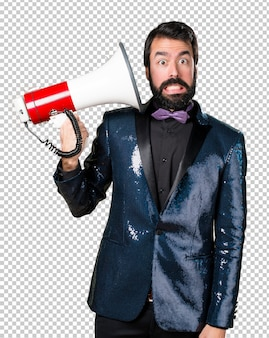 Handsome man with sequin jacket shouting by megaphone