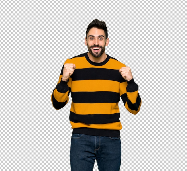 Handsome man with striped sweater celebrating a victory in winner position