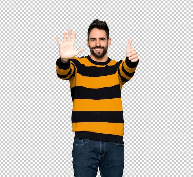 指で6を数えるストライプセーターを持つハンサムな男