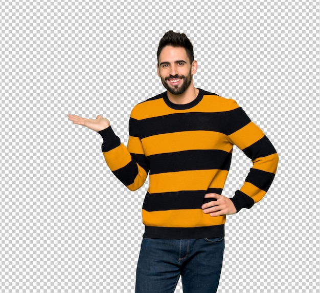 Handsome man with striped sweater holding copyspace imaginary on the palm to insert an ad