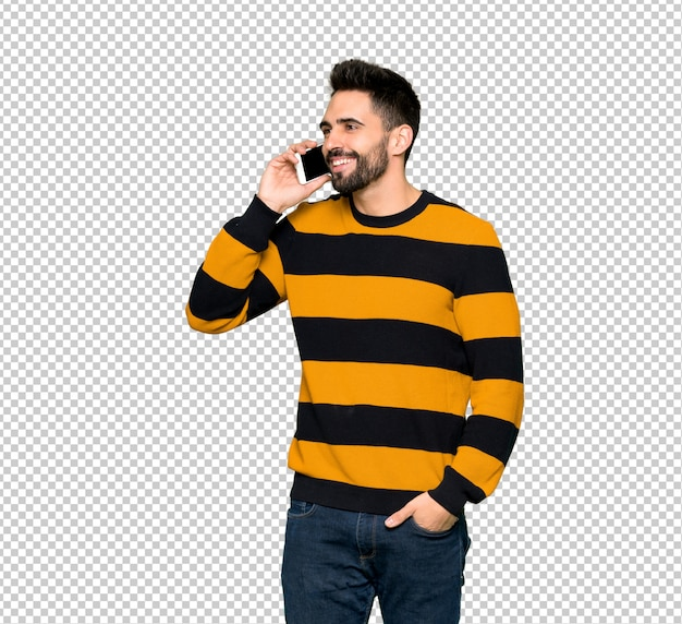 Handsome man with striped sweater keeping a conversation with the mobile phone