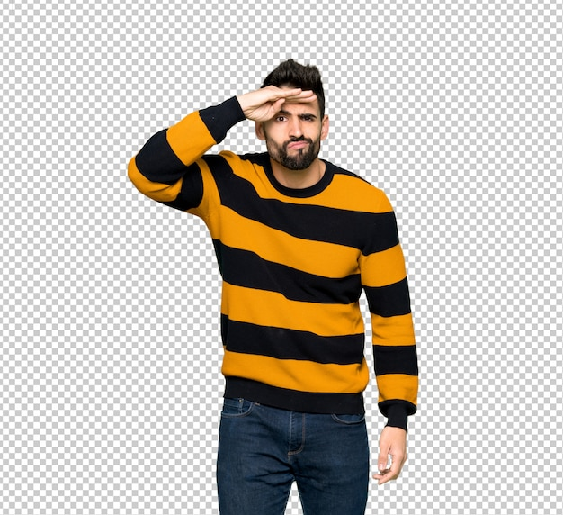 Handsome man with striped sweater looking far away with hand to look something
