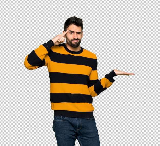 Handsome man with striped sweater making the gesture of madness putting finger on the head