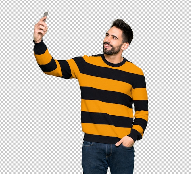 Handsome man with striped sweater making a selfie