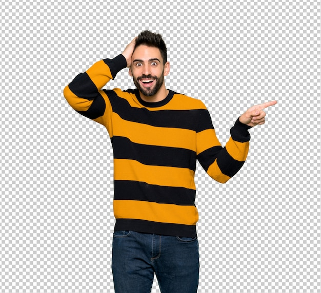 Handsome man with striped sweater pointing finger to the side and presenting a product
