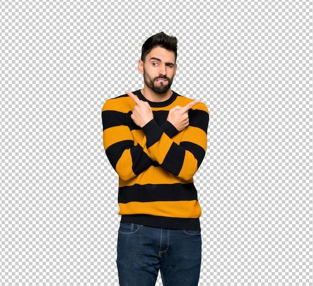 줄무늬 스웨터 의심 측면을 가리키는 잘 생긴 남자