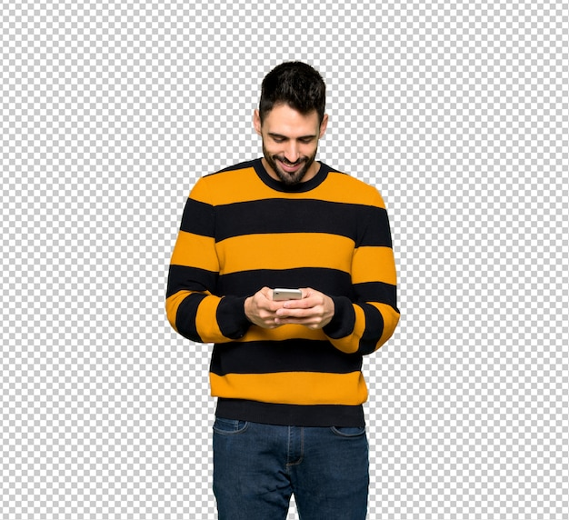 Handsome man with striped sweater sending a message with the mobile