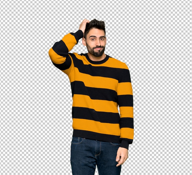 Handsome man with striped sweater with an expression of frustration and not understanding