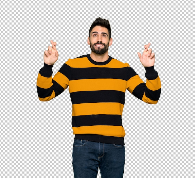 Handsome man with striped sweater with fingers crossing and wishing the best