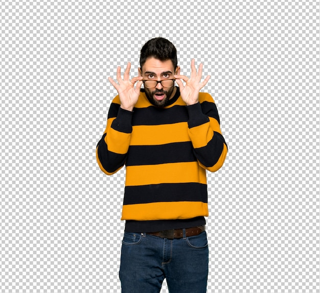 Handsome man with striped sweater with glasses and surprised