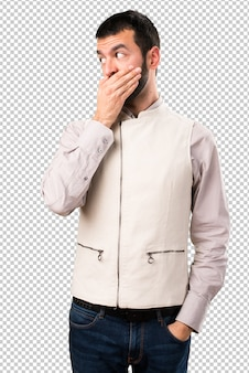Handsome man with vest covering his mouth