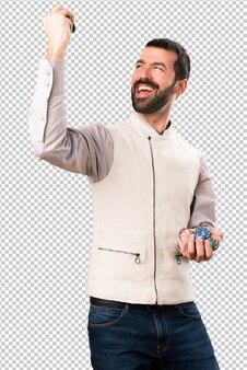 Красивый мужчина с жилетом держит фишки для покера