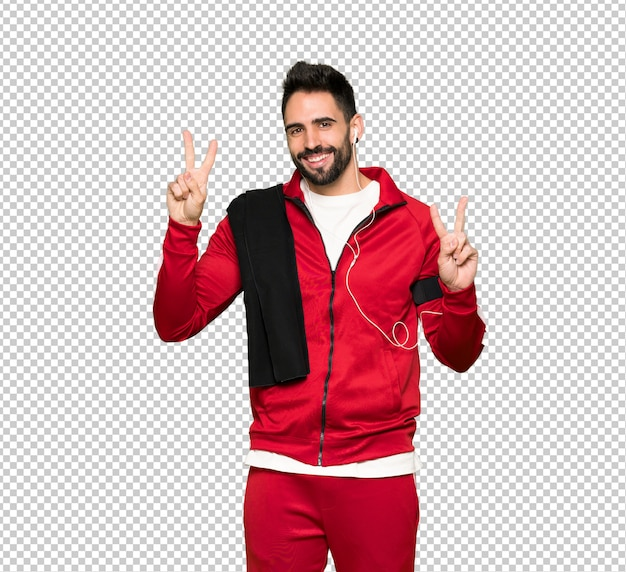 Handsome sportman smiling and showing victory sign with both hands