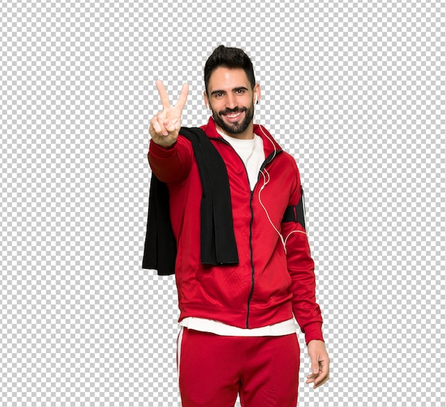 Handsome sportman smiling and showing victory sign