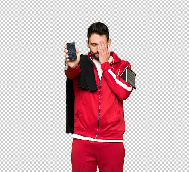 Handsome sportman with troubled holding broken smartphone