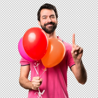 Handsome young man holding balloons and  counting one