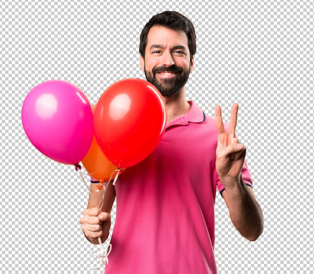 Handsome young man holding balloons and counting two