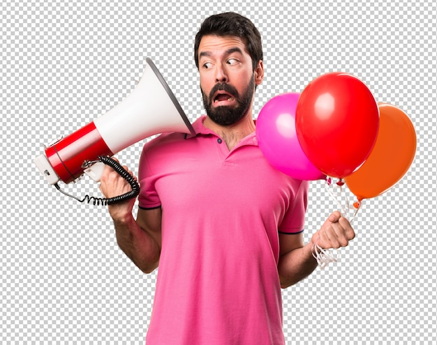Handsome young man holding balloons and  holding a megaphone