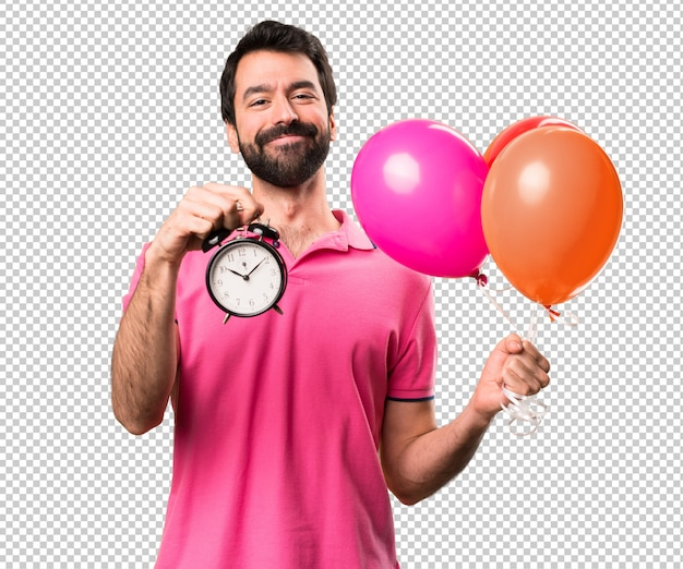 Handsome young man holding balloons and  holding vintage clock