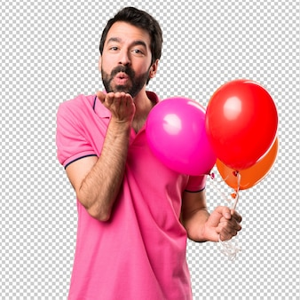 Handsome young man holding balloons and  sending a kiss