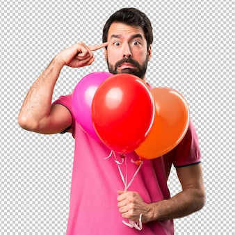 Handsome young man  making crazy gesture holding balloons