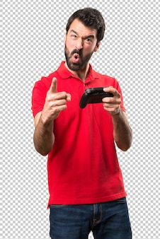 Handsome young man shouting and playing videogames