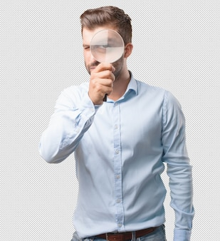 Handsome young man with magnifying glass