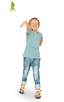 Happiness little boy smiling and flying paper airplane studio portrait