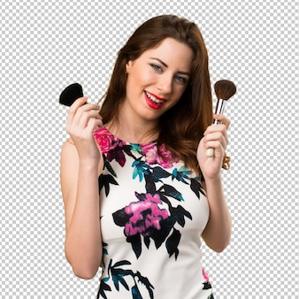 Happy beautiful young girl with makeup brush
