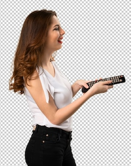 Happy beautiful young girl with a television remote Premium Psd