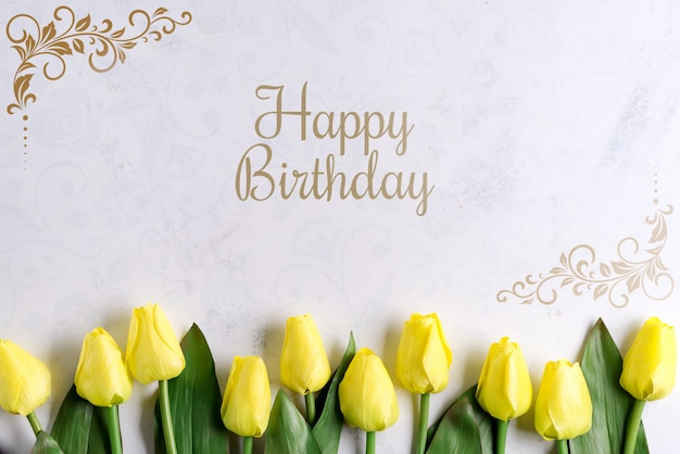 Happy birthday yellow tulip flowers on stone background, flat lay with copy space