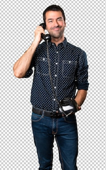 Happy brunette man talking to vintage phone