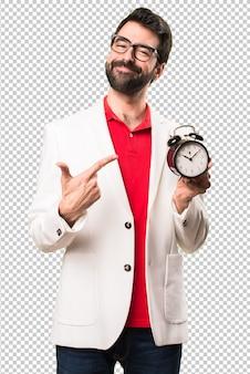 Happy brunette man with glasses holding vintage clock