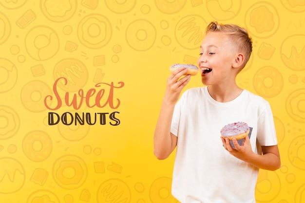 Счастливый ребенок ест пончик