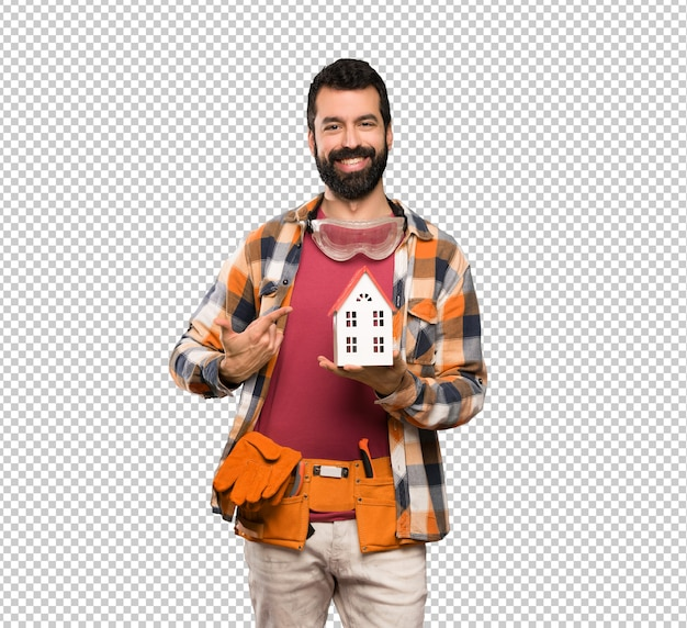 Happy craftsmen man holding a little house