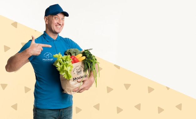 Happy delivery man holding a box with different vegetables with copy space