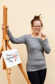 Счастливая девушка с синдромом дауна позирует с макетом холста