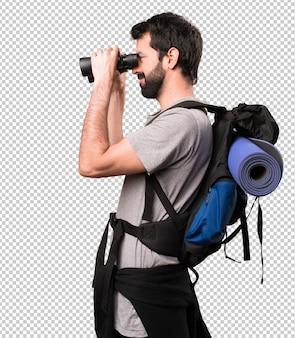 Happy handsome backpacker with binoculars