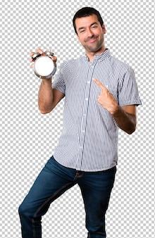 Happy handsome man holding vintage clock