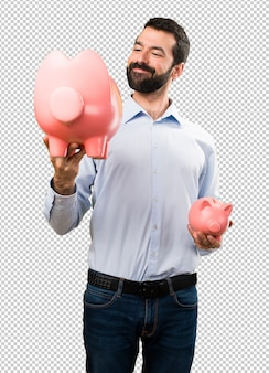 Happy Handsome man with beard holding a piggybank