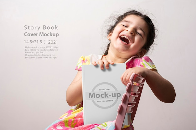 Happy little girl holding a funny story book with blank cover in front of body
