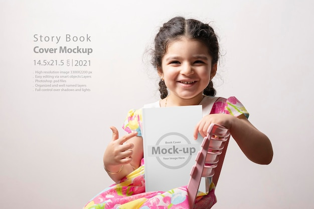 Happy little girl pointing to a story book with blank cover in front of her body